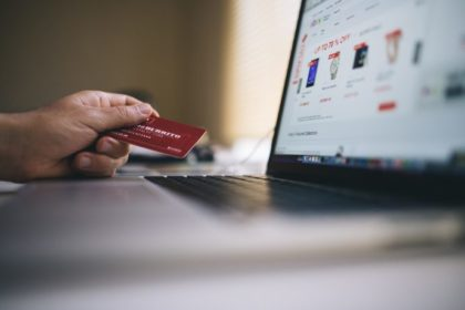 Laptopnutzer hält EC-Karte in der Hand